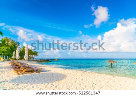 Beach chairs with umbrella at Maldives island, white sandy beach and sea #522581347