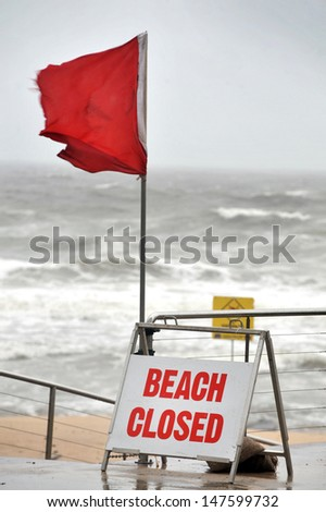 beach closed sign and red flag