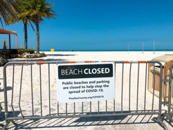 Beach closed sign. Warning of coronavirus or covid-19. Florida beaches. Palm Trees on the beach.