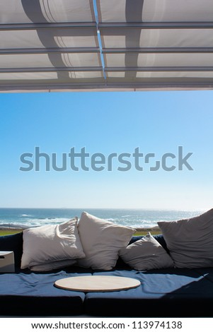 Beach club couch with ocean in the background