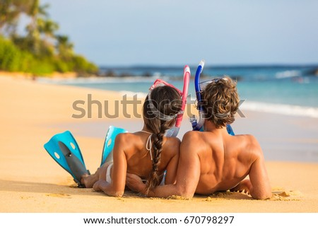 Beach couple relaxing on summer honeymoon vacation with snorkel equipment. People lying down on golden sand at sunset with diving mask, flippers sun tanning enjoying travel holiday lifestyle. #670798297
