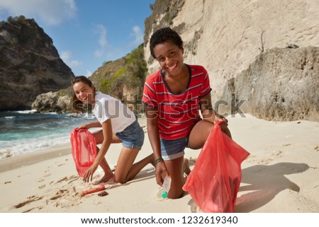 Beach environment and tidying up rubbish concept. Two cheerful volunteers collect garbage at coastline, pose against cliff background, smile as do good things for nature, being socially active #1232619340