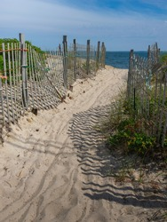 Beach fence with shadows at the entrance to the sea