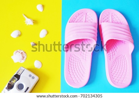 Beach flat lay photo. Retro camera, seashells and pink slippers on a yellow and blue background. Top view stock photography. Travel concept. Sea trip