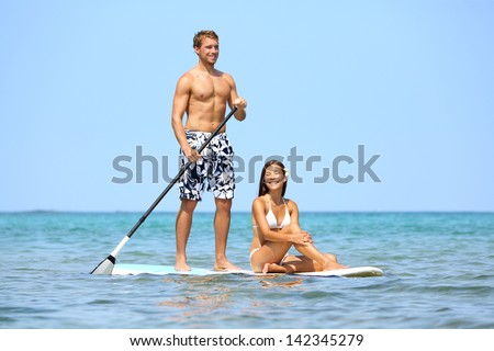 Beach fun couple on stand up paddleboard surfboard surfing together in ocean sea on Big Island, Hawaii Beautiful young multi-ethnic couple, mixed race Asian woman and Caucasian man doing water sport.