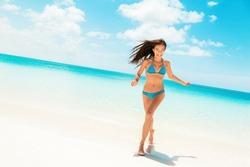 Beach fun happy Asian woman laughing running in blue bikini from ocean Caribbean travel destination. Slim body model enjoying summer holidays.
