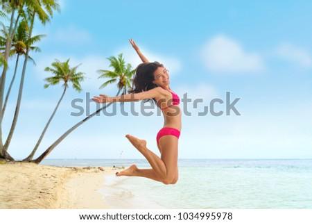 Beach fun summer vacation under the sun joyful happy bikini woman jumping of joy on Tahiti luxury travel destination. Asian girl happiness jump. #1034995978