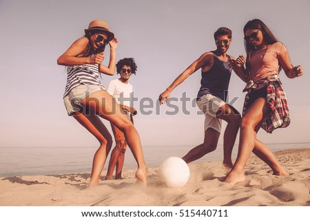 Beach fun with friends. Group of cheerful young people playing with soccer ball on the beach