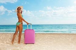 Beach girl with pink luggage near the sea
