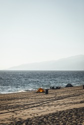 Beach goers on the sandy beach of California enjoying summer and sunset. Camping chairs and tents on the beach to block the sun.