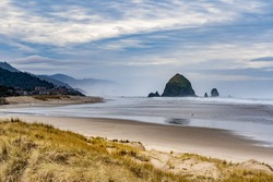 Beach grass and Haystack Rock and city of Canon Beach, Oregon