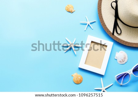 Beach hat and picture frame with starfish,Shell on blue table In the summer Asia,copy space,Top view,minimal style