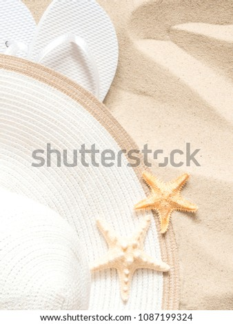 Beach hat, flip flops and starfish. Texture of light sand. The concept of a beach holiday. Summer concept.  Flat lay, top view, copy space