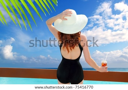 beach hat rear view woman cocktail tropical beach black swimsuit [Photo Illustration]