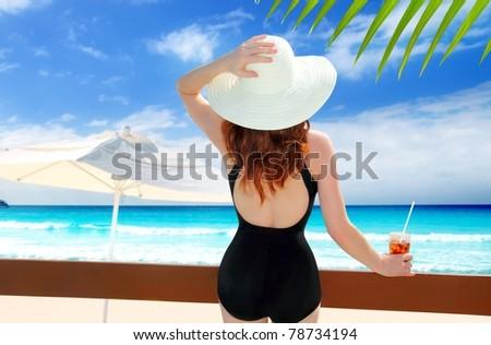 beach hat rear view woman cocktail tropical beach black swimsuit [Photo Illustration]