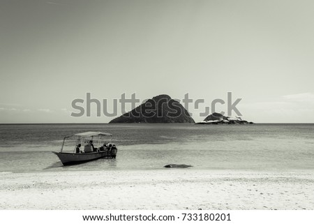 Beach, hill, boat and people in the beautiful sea in Perhentian Besar island, Malaysia, in black and white #733180201