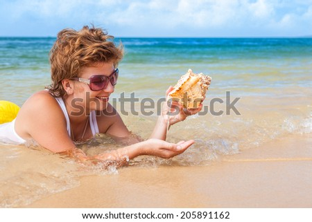 Beach holiday. Smiling happy woman lying in water on the beach and pours water from a large seashell