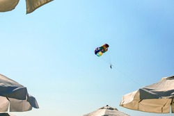 Beach holidays, vacations - multi-colored parachute with man soars in clear sky between the white beach umbrellas. Selective focus.