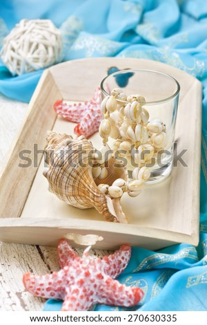 beach house decor, setting summer vacation : Candle in the form of starfish, shells, pareo on the wooden background