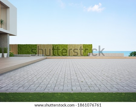 Beach house with empty cobblestone floor for car park. 3d rendering of green grass lawn in modern sea view home.