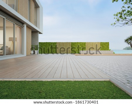 Beach house with wooden terrace near empty cobblestone floor for car park. 3d rendering of green grass lawn in modern sea view home.