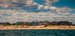 Beach houses and people on the beach in Point Pleasant, New Jersey.