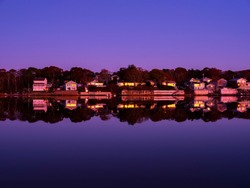 Beach houses and woods evenly reflected vertically on bluish purple sea water after sunset