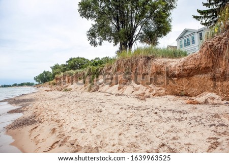 Beach houses on Lake Michigan, lake erosion dangerously close to the houses, focus on bluff in center of image Foto stock ©