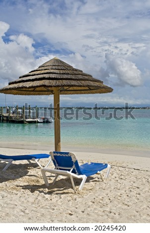 Beach hut with chairs on tropical shoreline at a resort.