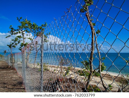Beach in Florida Keys blocked off by chainlink fence after it was destroyed by Hurricane Irma in 2017 #762033799