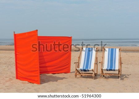 Beach in Holland with orange sun screen and chairs