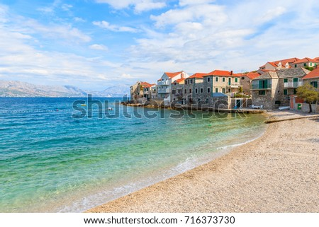 Beach in Postira town with old houses on shore, Brac island, Croatia