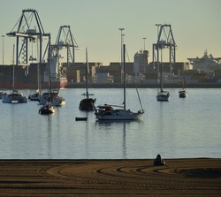 Beach in the foreground with woman sitting on the sand, anchored sailboats and port in the background, Las Palmas of Gran Canaria