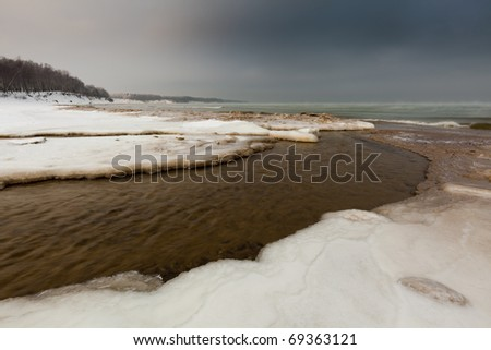 beach in winter ice-covered for the impending storm, with the river in the foreground