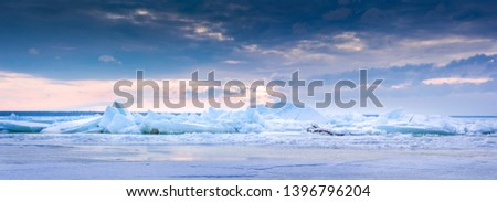 Beach in wintertime. Frozen sea, evening light and icy weather on shore like fairy tale country. Winter on coast. Blue sky, white snow, ice covers the land. #1396796204