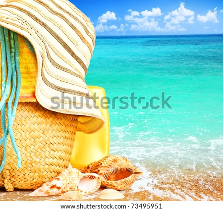 Beach items over blue sea conceptual image of summertime vacation & holidays
