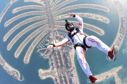 Beach jump. Freedom as a way of life. Parachutist performs an acrobatic trick in the Dubai air. Parachutist in white suit. Skydiver is in free fall.