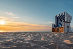 Beach landscape at sunset. North sea beach chair on white sand near seawater on Sylt island, Germany.