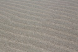 Beach landscape France: Fine sand drifted by the wind forming structures as rows or lines at the wide beach of Carnon-Plage near Montpellier at the Mediterranean, close-up, texture, blurred background