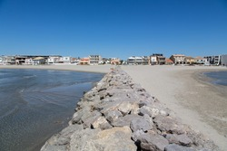 Beach landscape France: Long mole with huge stones protecting the sandy beach of Carnon-Plage near Montpellier with its clear non-polluted water and its family friendly waterside vacation rentals