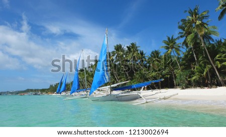 Beach landscape. Philippine white boats with bright-blue sails stand off the shores of the crystal clear sea on a sandy beach with green palm trees. Boracay, Philippines.