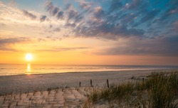Beach landscape with marram grass and the sun setting over the North Sea, on Sylt island, Germany. Summer landscape with empty beach and sunset.