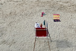 beach lifeguard sitting in chair watching beach goers safety