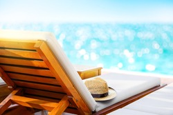Beach lounger with straw hat on the beach. Travel vacation concept.