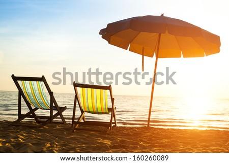 Beach loungers on deserted coast sea at sunrise, Thailand.