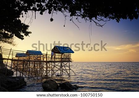 Beach nipa huts on bamboo stilts during sunset