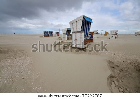 beach of St. Peter Ording at the german Atlantic coast with hooded beach chairs