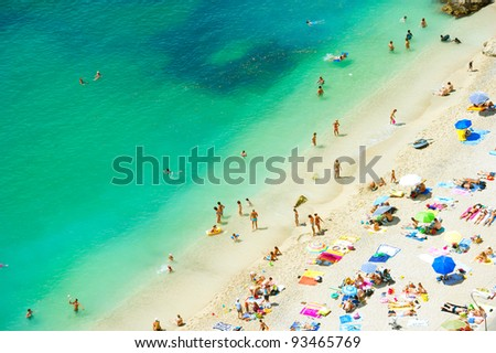 beach of the Cote d'Azur, mediterranean sea, with tourists with sunbeds and umbrellas on the hot summer day - stock photo