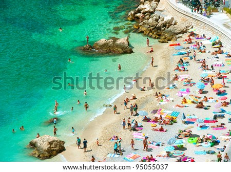 beach of the Cote d'Azur with tourists with sunbeds and umbrellas on the hot summer day #95055037