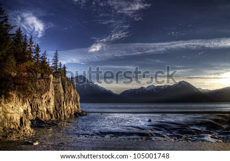 Beach on the Turnagain Arm near Hope Alaska at low tide with interesting patterns in the sand and cliffs illuminated by the evening light.